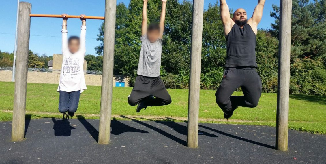 Three members hanging on pull up bars